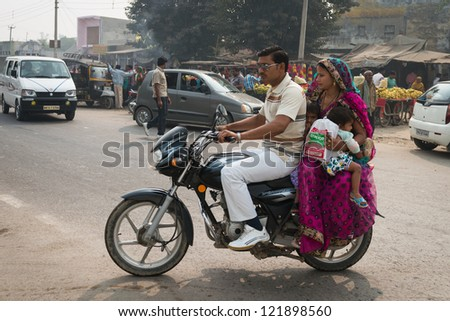 AGRA, INDIA - NOV 15: Indian family with two kids rides motorcycle on typical messy street in central India on Nov 15, 2012 in Agra, India. More than two person on one bike is widespread in India.