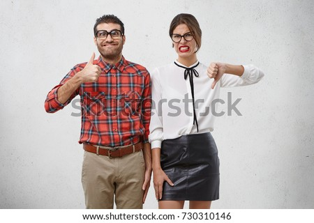 Agree and disagree concept. Two male and femae friends express different emotions as evaluate something. Cheerful wonk man raise thumb shows ok sign. Unpleased female model expresses dislike #730310146