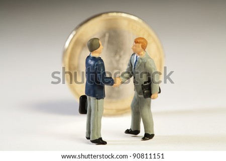 Agreement Among Member States On European Debt. Two miniature figurines of businessmen shake hands in front of an upright Euro coin on new treaty proposals.