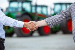 Agreement. Close up professional farmer with a modern combine. Confident, bright colors. Agriculture, exhibition, machinery, plant production. Senior man near his tractor with investor shaking hands.