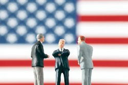 Agreement or negotiation in politics: Miniature figurines discussing about a subject in front of defocused United States of America flag. Business world concept with businessmen.