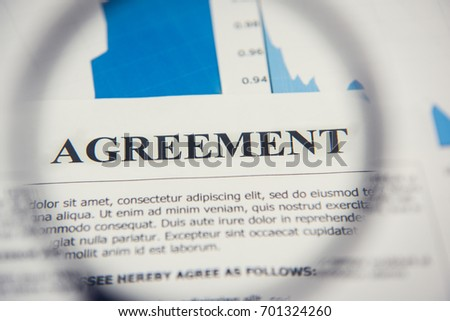 Agreement paper looking through magnifying glass - document reviewing and analysis concept