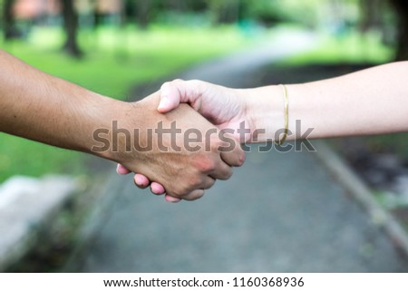 Agreements and friendships can happen anywhere, even in parks. Handshake is the promise of friendship and success. #1160368936