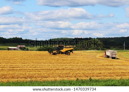 Agricultural background and rural life at summer concept. Scenic rural landscape with harvested wheat field, combine harvester, uploaded truck, farm buildings and beautiful cloudy sky at sunny day.