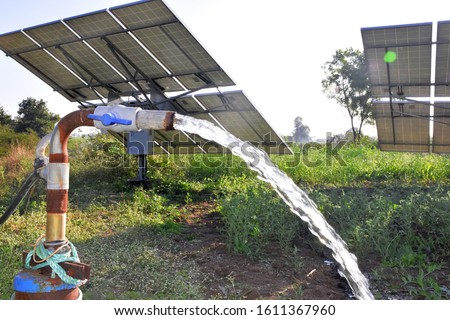 Photo of  agricultural equipment for field irrigation, water jet, behind which is solar panel's,