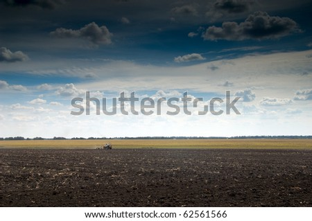Agricultural field with a tractor