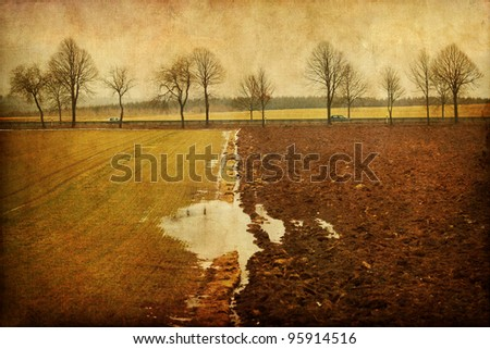 agricultural grunge textured landscape with a country road and cars with grunge - stock photo