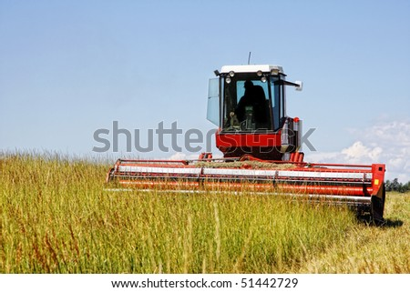 Agricultural image of a large mechanized Swather mowing a grass field to make quality grass hay bales for livestock feed (focus point on Swather). - stock photo