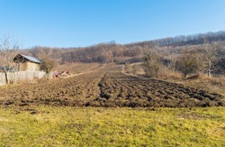 Agricultural land plowed. Plowed field, a forest on the horizon and blue sky. Beautiful landscape in the countryside