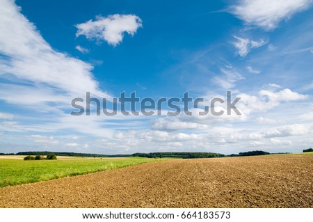 Agricultural landscape with plowed field, meadow and forest area under blue sky with some clouds