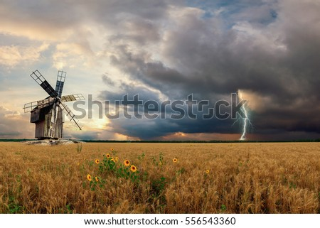 Agricultural landscape with wheat fields and vintage windmill, lightning and thunderstorm