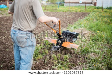 Agricultural machinery: cultivator for tillage in the garden. man Farmer plows the land with a cultivator, preparing it for planting vegetables, in a sunny garden #1101087815