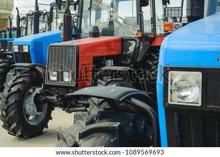 agricultural machinery, tractors stand in a row of blue and red. New working machines with square headlights
