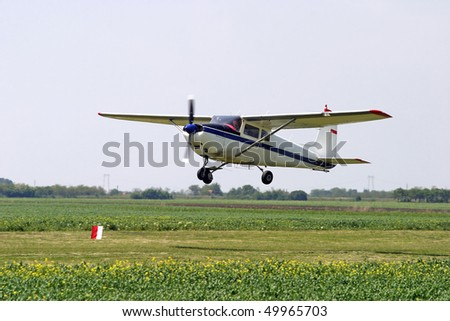 Agricultural plane is flying above green fields