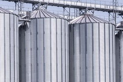 Agricultural Silo - building for storage and drying of grain crops. Industrial concept, silo tower over blue sky
