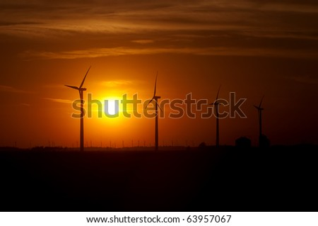 Agricultural silos of grain operation and turbines from a wind farm silhouetted by setting sun