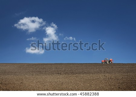 agricultural tractor cultivating on field with blue sky
