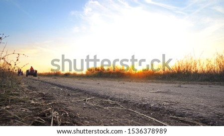 Agricultural tractor transporting harvested crops on rural road against sunset with combine harvester at background
