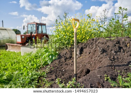Agriculture and agriculture. A shovel is stuck in the ground against the background of a compost pit and a tractor. Summer sunny day