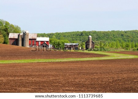 Agriculture and farming background.Scenic countryside spring landscape with farm buildings and ted barns on a woods background, freshly plowed field on a foreground.Midwest USA,Wisconsin,Madison area.