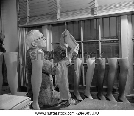 Agriculture Department fabric technician examines the cotton stockings that would replace those made by Japanese silk, after FDR froze all Japanese credits in the United States. July 1941.
