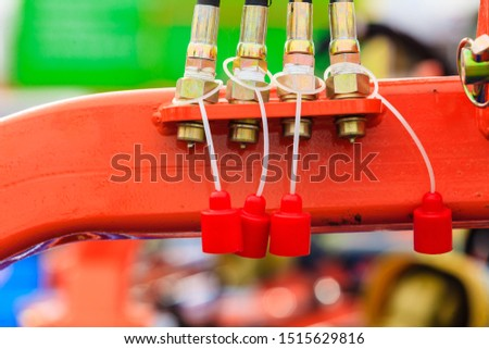 Agriculture equipment concept. Four hydraulic, pneumatic pipes on red machinery with plugs