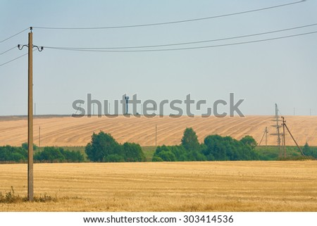Agriculture field after harvesting and electric poles. Rural scene.