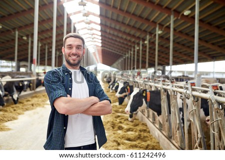 agriculture industry, farming, people and animal husbandry concept - happy smiling young man or farmer with herd of cows in cowshed on dairy farm