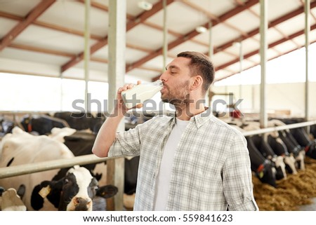 agriculture industry, farming, people and animal husbandry concept - happy young man or farmer drinking cows milk from bottle in cowshed on dairy farm