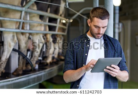 agriculture industry, farming, people, technology and animal husbandry concept - young man or farmer with tablet pc computer and cows at rotary parlour system on dairy farm
