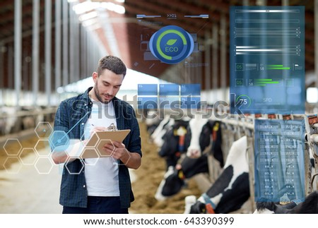 agriculture industry, people and animal husbandry concept - happy young man or farmer with clipboard and cows in cowshed on dairy farm