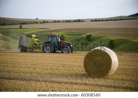 Agriculture landscape with straw bale and a tractor