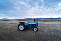 Agriculture stock picture. A small tractor on a field during the sunset time. Agriculture in Iceland, Scandinavia. Background photograph of a tractor