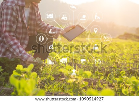 Photo of  Agriculture technology farmer man using tablet computer analysis data and visual icon.