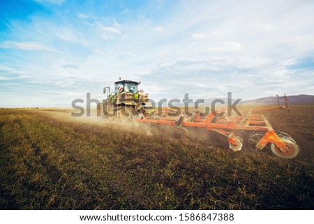 Agriculture. The tractor prepares the ground for sowing and cultivation. Agronomy, the concept of farming. Agricultural machinery for fields, Work of a plow on the field. New modern tractor. #1586847388