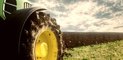 Agriculture. Tractor plowing field. Wheels covered in mud, field in the backround. Cultivated field. Agronomy, farming, husbandry concept.