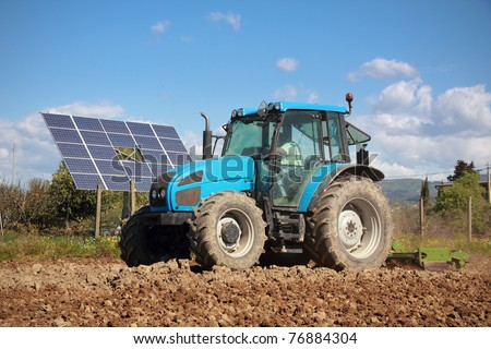 agriculture, tractor working on a field with photovoltaic solar panel in background