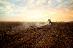 Agriculture use tractor plowing land field in the backround. Cultivated field. Agronomy, farming, husbandry .Tractor working on farm at sunset,modern agricultural transport,farmer working in the field