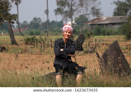 Agriculturist male with loincloth wrapped over the head sitting relax and cross one's arm at the nature. Stock fotó ©