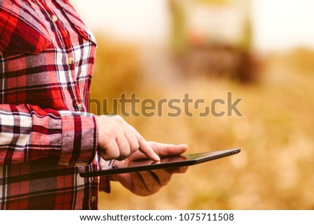 Agronomist farmer using tablet computer in corn field during harvest. Smart farming is usage of modern technology in agricultural production.