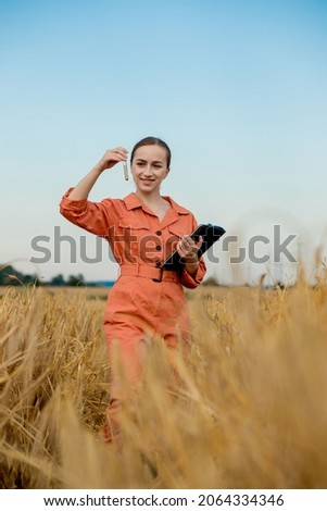 Agronomist holding test tube with barley grains in field, closeup. Cereal farming, oncept of wheat testing.