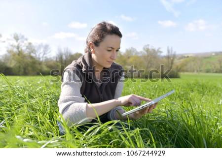 Agronomist in crop field using digital tablet