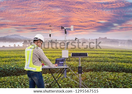 Agronomist using tablet computer collect data with meteorological instrument to measure the wind speed, temperature and humidity and solar cell system in tea agricultural field, Smart farm concept #1295567515