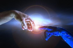 AI hand reaches towards a human hand as a spark of understanding technology reaches across to humanity. Artificial Intelligence concept copy space area. Blue cyborg arm and flare science background