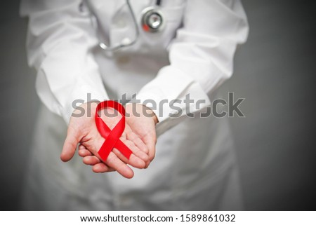 AID, HIV red ribbon. Symbol of awareness, charity, support in disease, illness, ill. A female doctor holding red ribbon in arms. AIDS, HIV. Medical health care, help and hope.