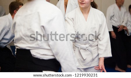 Aikido athletes in white kimono train on blue tatami. Girl with a white belt, a beginner and experienced man with a black belt