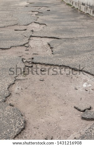 Ailing pothole road requires important infrastructure investment. Neglected street with potholes damage shows accident traffic risk through holes in asphalt due poverty or investment maintenance jam