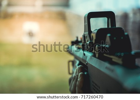 Aiming of tactical shotgun with red dot sight in the shooting range. #717260470