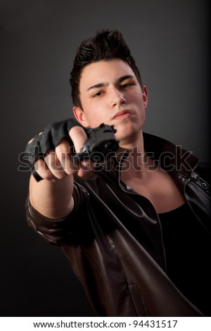 Aiming. Serious man with a gun on a black background