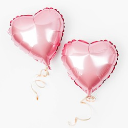 Air Balloons of heart shaped foil  on white background. Love concept. Holiday celebration. Valentine's Day or wedding/bachelorette party decoration. Metallic balloon